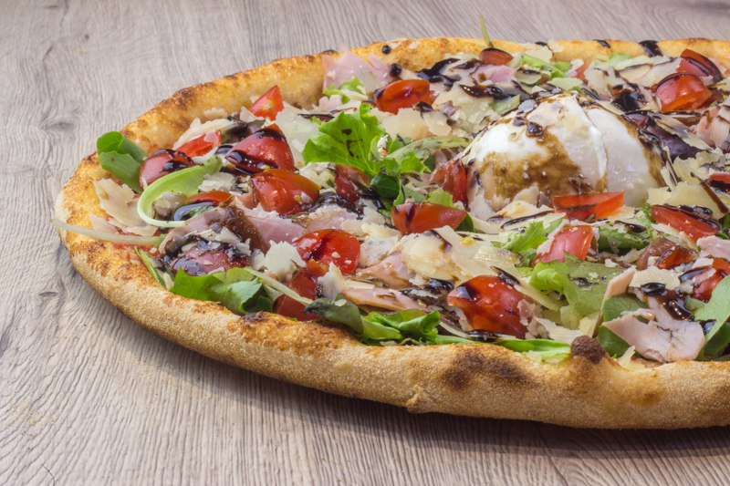 la pizza top garniture disponible chez l'authentique pizza à nice cimiez la fraicheur ingrédients Tomate Mozzarella, Mesclun, Buffala, Jambon Cuit*, Tomate cerise, Copeaux de Parmiggiano Reggiano (22/24 mois d'affinage), Balsamique
